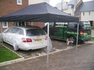 Fixing a car in the rain in Shoreham